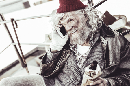 Communication with phone. Unhygienic man with tangled hair and bottle in hand calling his friend with smartphone. Stok Fotoğraf