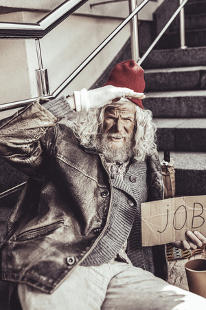 See you. Caucasian old homeless man seeing friend distantly and watching him with hand on forehead while holding cardboard.