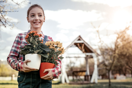 Colorful flowers. Young cute girl wearing in county style clothes and taking several colorful flowers in pot