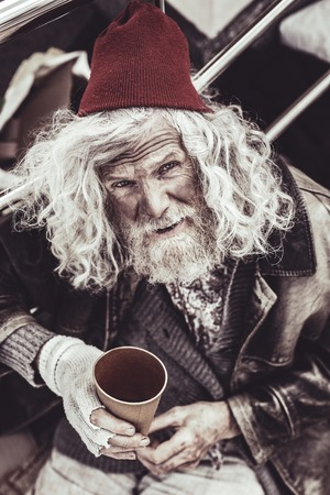 Today misfortune. Nobody throwing money in plastic cup for desperate old beggar today. Stok Fotoğraf