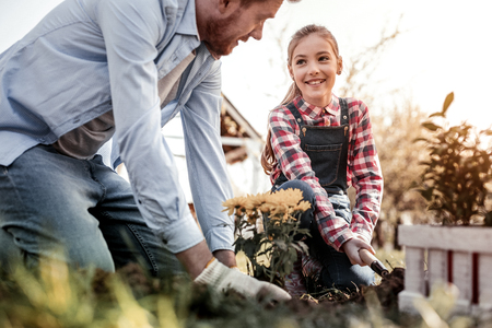 Stunning father. Smiling long-haired daughter helping his stunning father who teaching daughter how planting tender flower