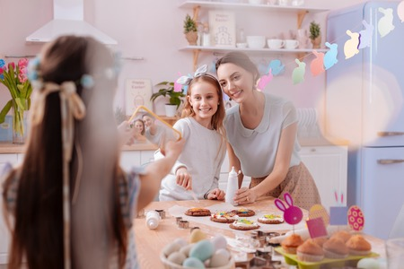 Look at us. Charming brunette woman feeling happiness while spending weekend with her kids Stock Photo