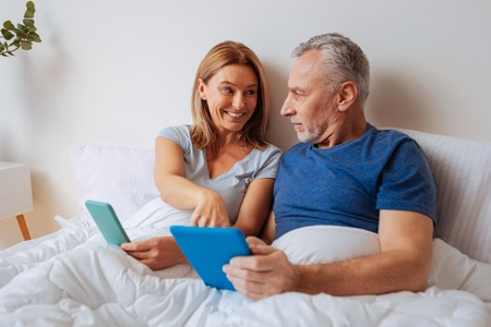 Tablets in bed. Beaming loving wife talking to her grey-haired husband while using tablets in bed