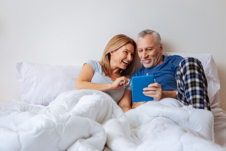 Comedy with husband. Blonde-haired wife feeling entertained while watching comedy with husband in the bed