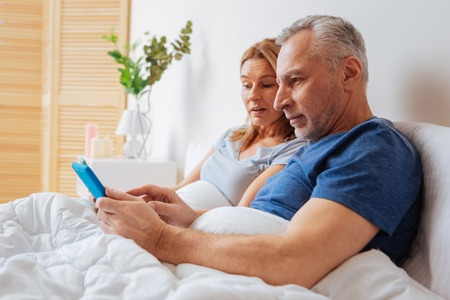 Showing news. Grey-haired husband showing morning news on tablet to his wife while lying in bed
