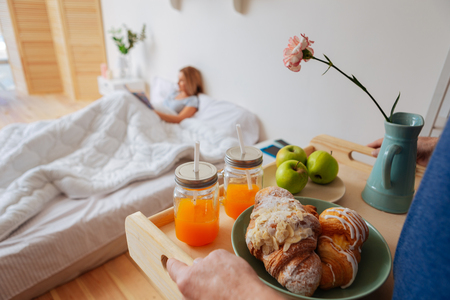 Croissants and fruits. Wife lying in bed while husband bringing tray with croissants and fruits in the morning Stock Photo
