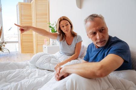 Kategorische Ehefrau. Grauhaariger Ehemann hört nicht auf seine kategorische emotionale Frau