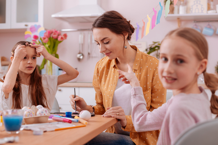 My inspiration. Concentrated young woman sitting between her daughters and painting Easter eggs Stock Photo