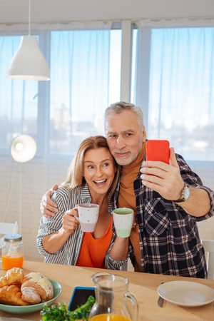 Selfie together. Funny mature couple holding cups of tea while making selfie together in the morning
