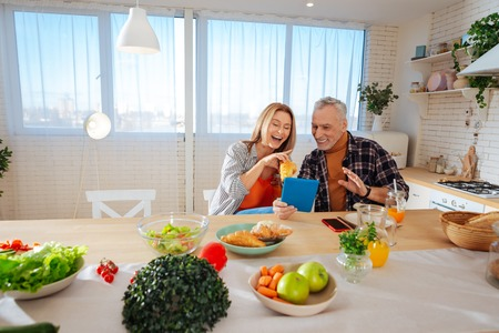 Beaming couple. Beaming mature couple having much fun while enjoying breakfast at home