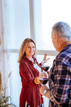 Wine from husband. Blonde-haired wife wearing stylish blouse taking glass of red wine from husband