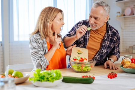 Eating cucumber. Funny bearded husband eating piece of cucumber while cooking salad with wife Banque d'images - 119908713