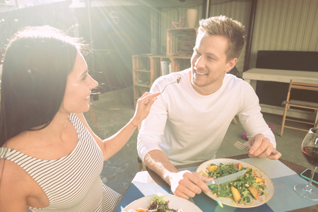 Together in restaurant. Joyful appealing girl carrying fork with food and proposing to her boyfriend while having lunch together Stok Fotoğraf