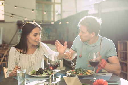Romantic dinner. Shameless long-haired girl stealing pieces of salad from plate of her confused male partner Stock fotó