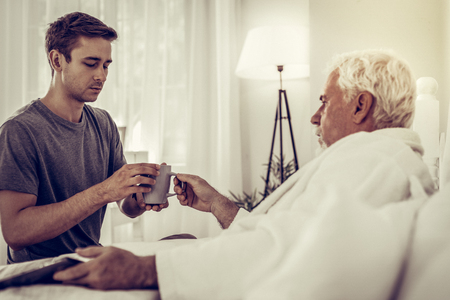 Son sitting at bedside of father. Focused upset appealing mature man wearing grey t-shirt passing the tea cup to his aging white-haired ill father in bed