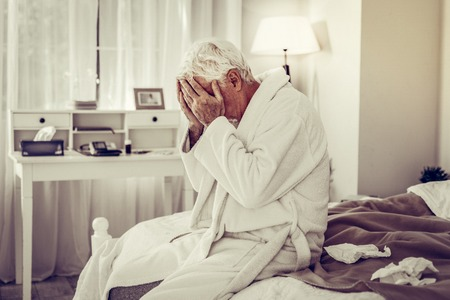 Ill man sitting on bed. Sick elderly man in white warm gown closing face with hands and sitting on bed full of paper tissues