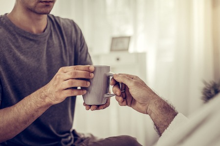 Handing the tea cup. Close-up photo of adult man wearing stylish grey t-shirt handing the beige tea cup to ill person in bed