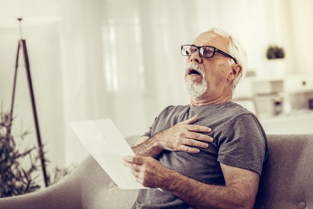 Shocked man with papers. Shocked elderly silver-haired nice-appealing man having a heart attack after reading of medical papers