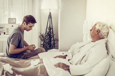 Measuring temperature. Young-adult handsome son holding thermometer in hands and checking its indicators while his elderly grey-haired ill father lying in the bed. Reklamní fotografie
