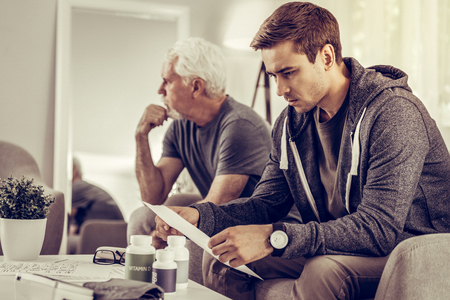 Considering medical assessment. Concerned upset vicennial son considering the medical assessment of his sick elderly sad silver-haired father sitting on the sofa beside him