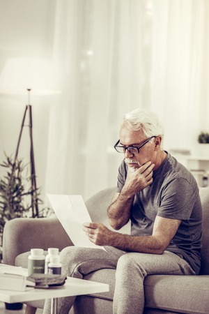 Carefully considering documents. Aged silver-haired handsome gentleman wearing stylish glasses and basic grey t-shirt carefully considering documents that holding in hands