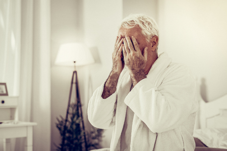 Closing face with hands. Portrait of sick aging white-haired male in white home gown palming face at bedroom