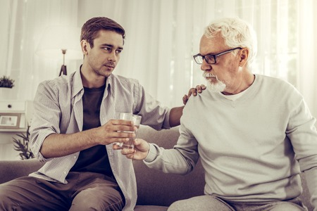 Handing glass of water. Supporting helpful handsome adult dark-haired man in shirt handing the glass of water to elderly grey-haired tired mister in glasses sitting on the sofa Reklamní fotografie