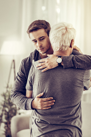 Hugs for relative. Twenty-years-old nice-appealing short-haired kind man hugging ill upset old grey-haired relative