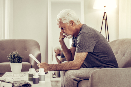 Reading prescription at home. Profile photo of elderly pleasant grey-haired man in grey t-shirt sitting on sofa and carefully reading a medical prescription Reklamní fotografie