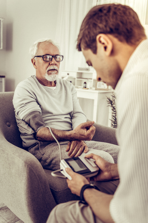 Measuring the blood pressure. Adult dark-haired son carefully taking the blood pressure with meter of his old silver-haired dad sitting in the chair