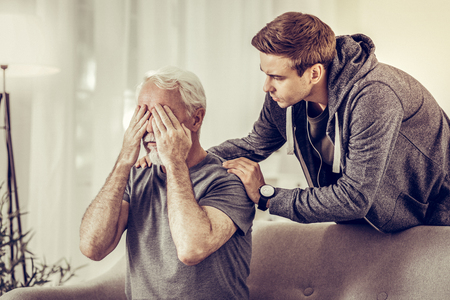 Calming hugs. Young appealing short-haired upset man calmingly hugging ill sorrowful elderly grey-haired grandfather