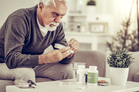 Sick old man with pills. Portrait of elderly ill grey-haired man holding pills box in hands sitting at table full of pills