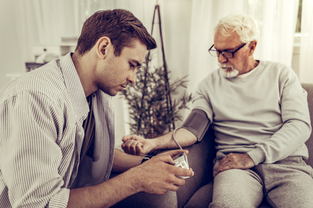 Taking the blood pressure. Young-adult handsome brown-haired son wearing sandy shirt taking the blood pressure of his elderly grey-haired father sitting on the sofa