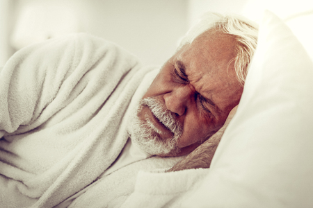A man in pain. Close-up portrait of an elderly bearded grey-haired wrinkled man in white gown experiencing pain Reklamní fotografie