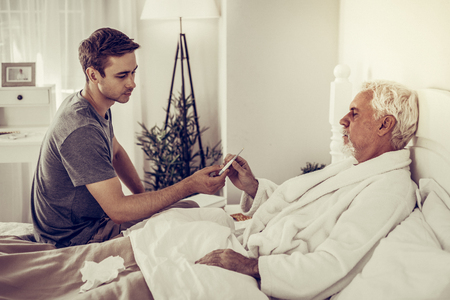 Ill man in bed. Young-adult good-looking son handing the thermometer to his aged silver-haired ill father lying in the bed for temperature measuring Reklamní fotografie