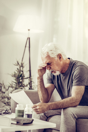 Shocked elderly man. Aged sad silver-haired mister in grey t-shirt sitting on sofa and clutching his head in shock after reading medical assessment