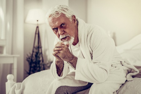Old man with black eye. Portrait of elderly grey-haired ill men with black eye wearing terry-loop gown concernedly sitting on the white bed Reklamní fotografie