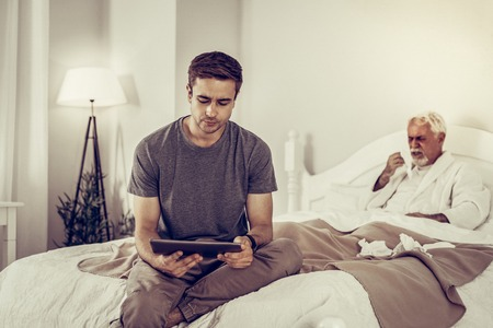 Helping to ill person. Concerned appealing short-haired male in grey t-shirt holding tablet while his sick elderly white-haired and bearded grandfather coughing in the bed