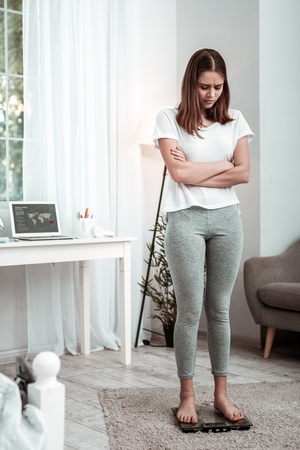 Putting up weight. An upset young woman standing on the weights Stockfoto