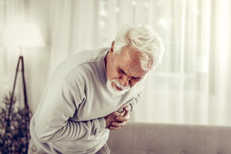 Doubling up with pain. Aging handsome grey-haired gentleman wearing glasses and beige pullover doubling up with heartache at living-room Reklamní fotografie