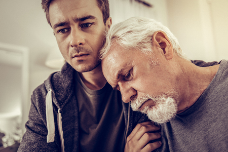 Sharing grieve with son. Portrait of aging grieving man with white beard and hair leaning his head on the shoulder of his v upset son