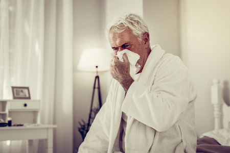 Old man with a running nose. Old ill man with white hair and beard in white terry-loop gown blowing his nose using paper tissue