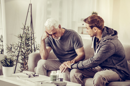 Comforting sick person. Young-adult short-haired appealing son in sporty clothing comforting elderly grey-haired upset sick father at living-room.