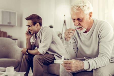 Indifferent father-son relationship. Old grey-haired wrinkled ill man taking pills from pillbox while his twenty-years-old beaming joyful son in glasses indifferently having a phone call.