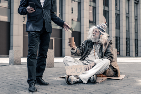 Supporting poor homeless. Smiling grey-haired dirty jobless man sitting on ground and begging pedestrians for money
