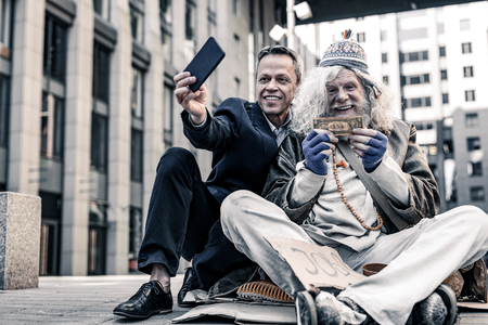 Excited old homeless. Vain rich man in costume making selfie of donation money to desperate poor man
