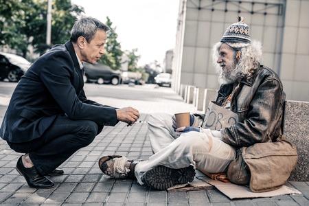 Conversación sincera. Agradable hombre rico de pelo corto en traje apoyando a los desamparados miserables mientras está sentado en el suelo de la calle Foto de archivo