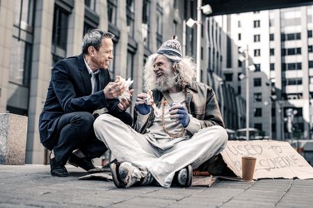 Biting pieces. Beaming good-looking man having pleasant conversation with dirty homeless while sitting nearby Фото со стока