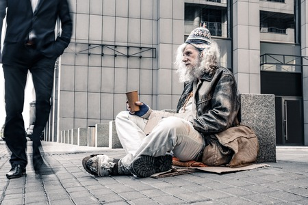 Long-haired poor man. Miserable grey-haired old homeless motionlessly sitting on cold ground while citizens going through
