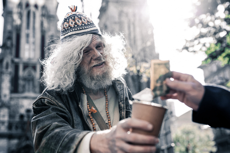 Generously giving money. Dirty long-haired homeless wearing funky clothes and asking for money with used coffee cup
